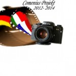 "The flags of Italy, France and Germany are presented like a roll of film of an older camera. Behind the flag roll are two normal reels, all reels are behind the camera. Above the camera is the logo ""Comenius Project 2012-2014""."