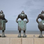 "These are three iron statues. I took this picture on the beach in Rotterdam. The three statues are looking at the North Sea. They remind us of the three Wise Monkeys who embody the proverbial principle to ""See no evil, hear no evil, speak no evil"". I like it because of the contrast between the sea, nature, and modern art. It was surprising to see these statues on the beach. Tourists are surprised when they see them. The City had these statues installed on one of the most popular beaches of the area to attract more tourists and make the site different from all the other beaches of the world. Thus, instead of coming to this beach merely to see the North Sea, tourists come to enjoy art and a pleasant moment outside."
